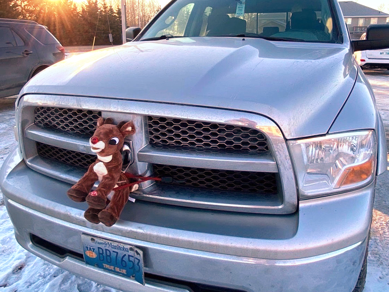 A stuffed rudolph toy tied to the grill of the truck