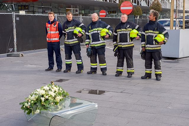 Several emergency responders stand in line with a wreath on the ground