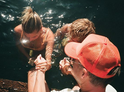 Justin Bieber and his wife getting baptized in a lake.