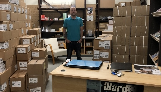 Ryan Rempel in his warehouse with Bibles in boxes