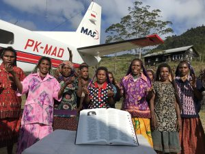 A group of people stand behind a large Bible in their own language, and in front of a plane