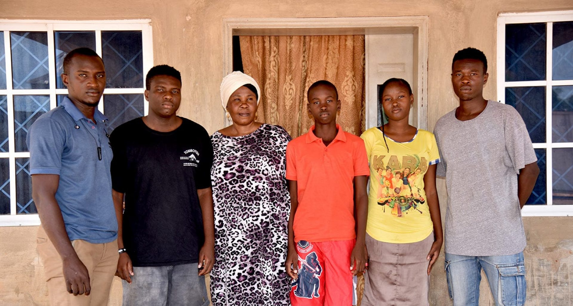 A woman stands with 5 children in front of a house