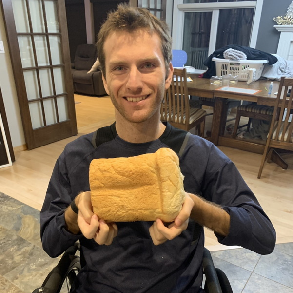 A man holds his loaf of bread
