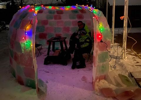 Ice igloo lit up at night with bright coloured blocks