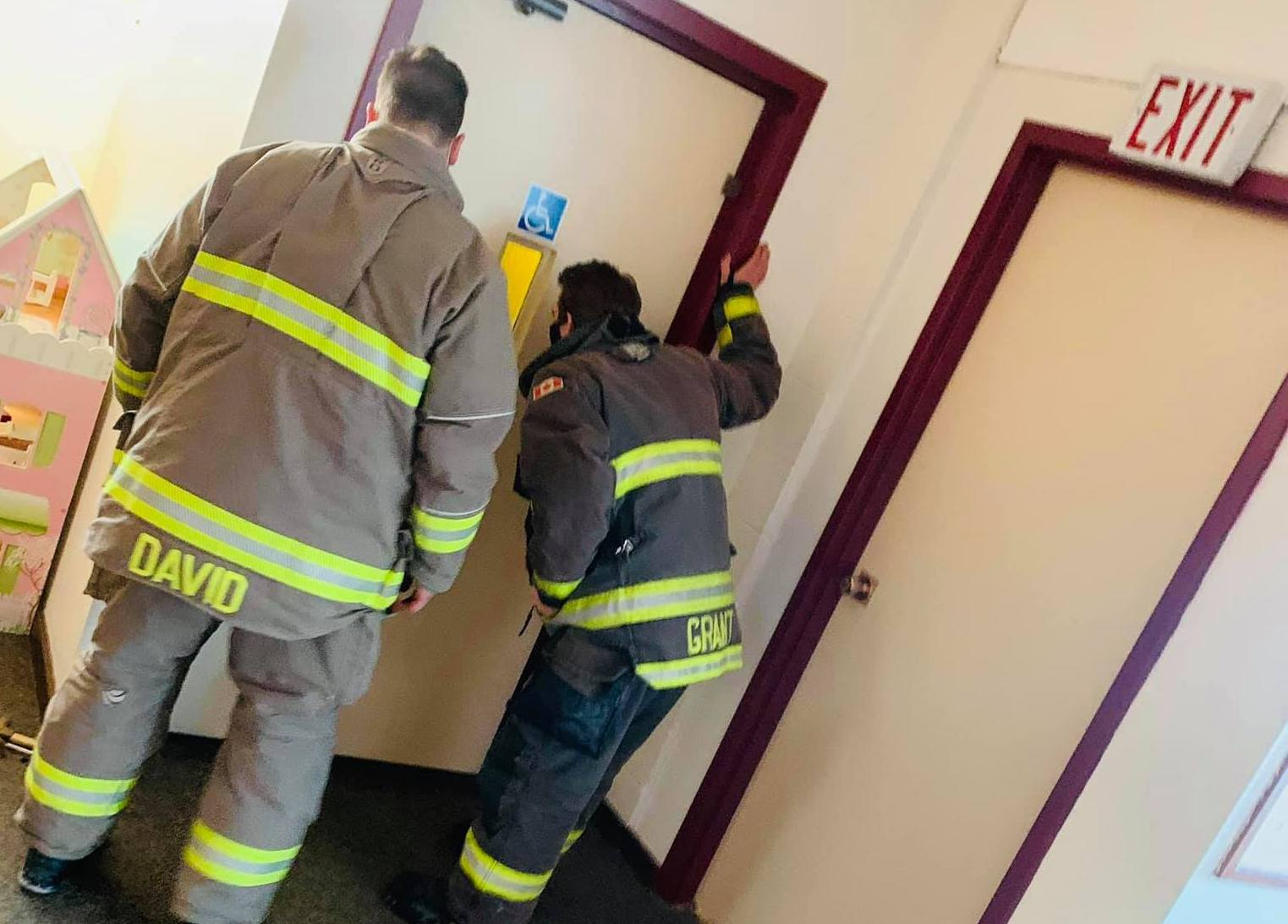 Firefighters stand outside the elevator door
